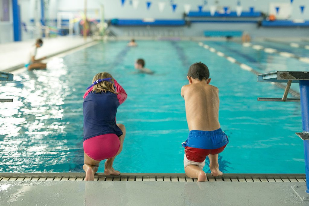 Two children in swim lessons learning how to dive into the pool